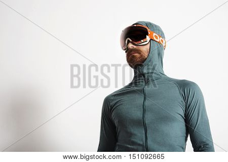 Young fitted bearded male athlete in baselayer thermal suite wears snowboarding googles, poses isolated on white background