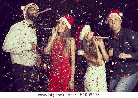 Two beautiful young couples having fun at New Year's party dancing and blowing party whistles