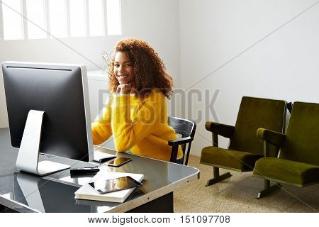 Charming young black lady working in small industrial office in front of big window, looking at camera with smile while working on her generic computer