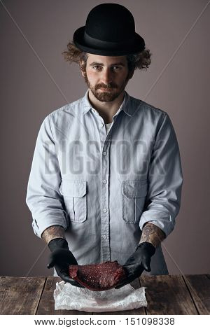 Weird young jewish butcher man with curly hair and beard wearing a too small derby hat and faded denim shirt offers a kosher raw steak in his hands over a wooden table.