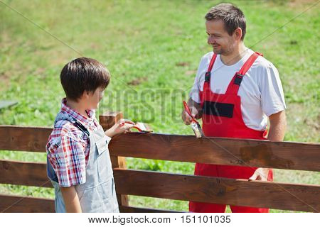 Father and son painting the fence in the sunny garden - working together, focus on the boy