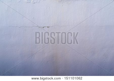 the abstract textured background of an old surface of the plastered wall of a motley violet color tonality