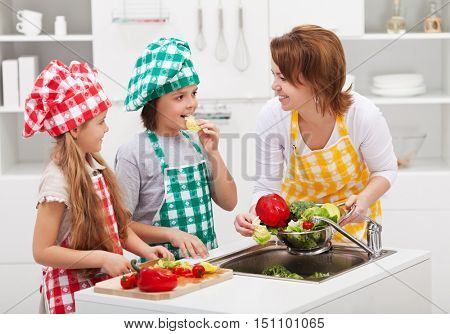Kids and woman in the kitchen preparing the vegetables for a meal - washing the salad ingredients
