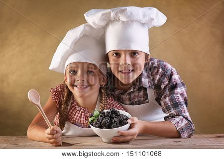 Eat right concept - kids with chef hats holding blackberries in a bowl