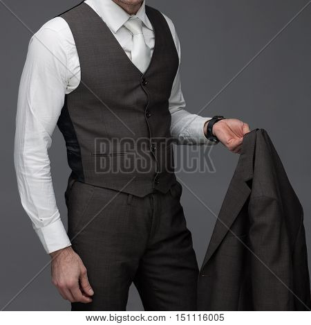 Business man standing with jacket in his hand on a grey background stock picture
