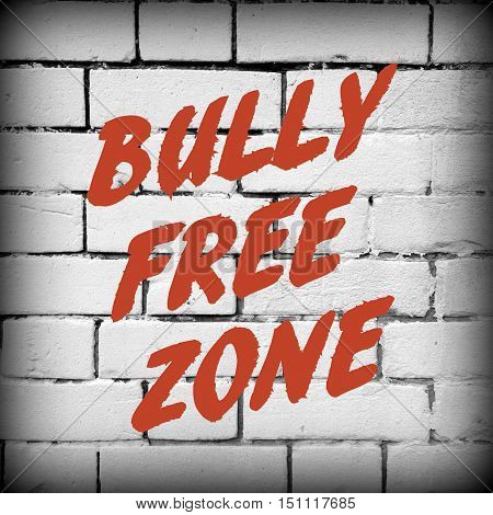 The words Bully Free Zone in red text on a black and white brick wall with a vignette added for effect