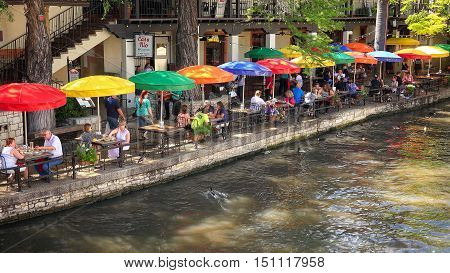 SAN ANTONIO, TEXAS - APRIL 14: Tourists eating lunch along the historic San Antonio River Walk in downtown San Antonio, Texas on April 14th, 2016.