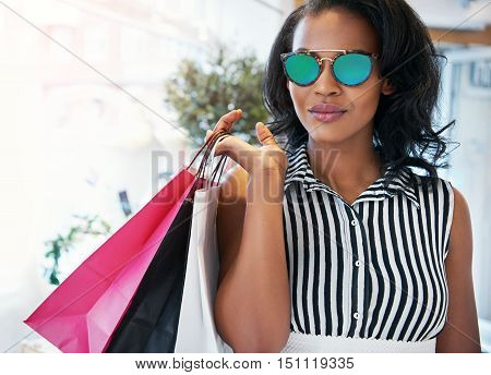 Attractive stylish modern young African woman shopping for clothes in a boutique standing with her purchases in bags over her shoulder