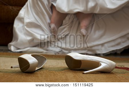 Wedding shoes on the floor women's foot in nylon stockings and white dress on the background.Bride is taking off her wedding shoes