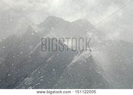 Heavy snowing, focused on the snowflakes, slightly blurry mountains in the background