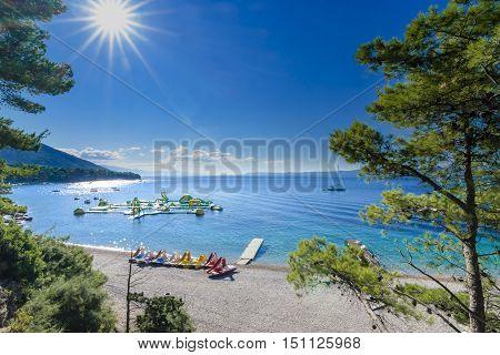 BOL, ISLAND BRAC, CROATIA - JULY 17, 2016: Zlatni rat beach crowded with swimmers, surfers and boats in high season