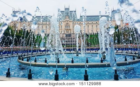The gush of water of a fountain in front of a beautiful cultural palace in Iasi city Romania