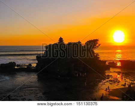 Tanah Lot and sea waves in golden sunset at Bali