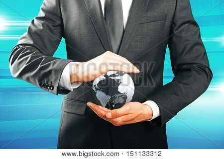 Closeup of businessman hands holding small terrestrial globe on blue background. Eco friendly business and environment protection concept