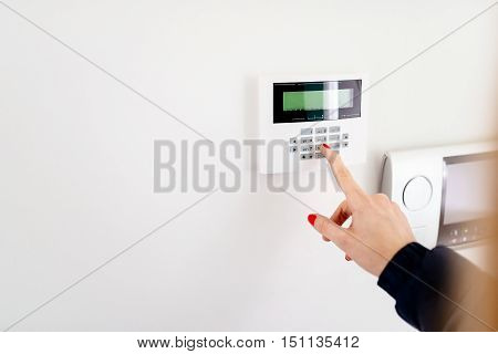 Young Woman Entering Security Code On Keypad