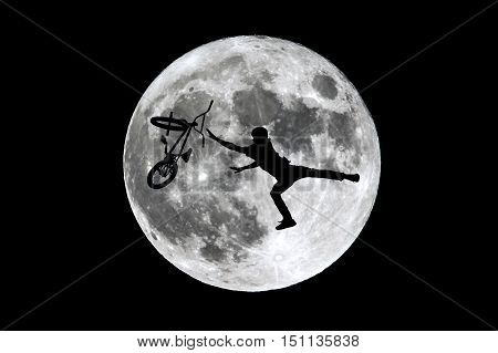 The full Moon is seen isolated on a black background. High contrast high resolution image taken with a full frame dslr camera. Free style biker silhouette jumping in front of the moon.