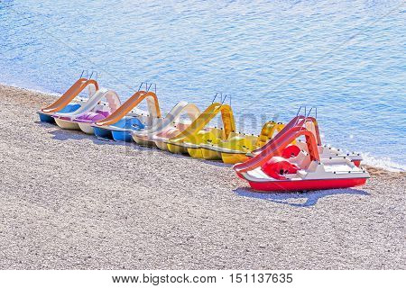 Pedal boats; Pedaling boats on beach; copy space