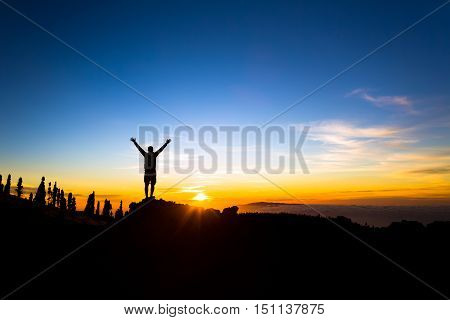 Man with arms outstretched celebrating beautiful inspiring sunset in mountains. Male hiker or climber with hands up enjoy inspirational landscape view on rocky trail on Tenerife Canary Islands.