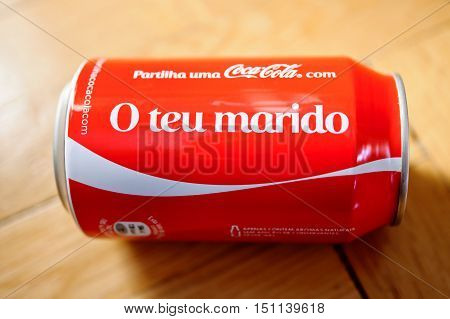 PARIS FRANCE - NOV 5 2016: Coca-Cola can with inscription in portuguese language O Teu Marido wich translates as To Your Husband against wooden background
