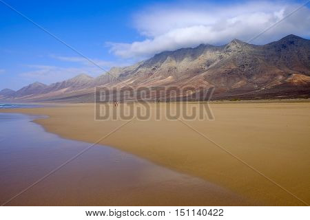 View on a beach Cofete with golden sand water reflections mountains with couds covering their tops and an unknown couple walking along the beach on the Canaty Island Fuerteventura Spain.