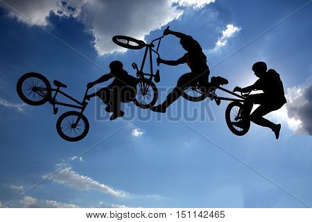 An extreme rider is making a free style jump from a ramp. The young boy with his bicycle is seen as a silhouette in front of the sun. Multiple exposure image. Clouds.