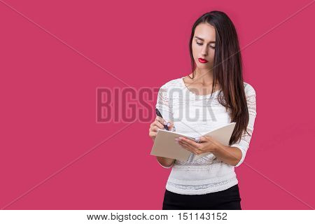 Serious gilr in white blouse standing against red background and writing in her notebook with spring. Concept of journalism. Mock up