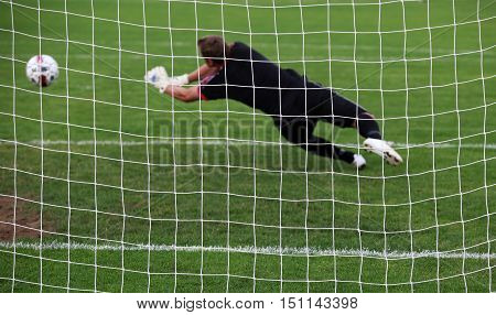 Soccer football goalkeeper making diving save in pitch