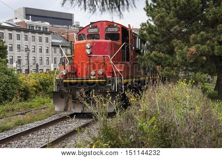 Red train engine approaching on railroad tracks