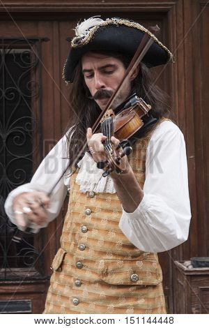 A man in 17th century clothing playing a violin