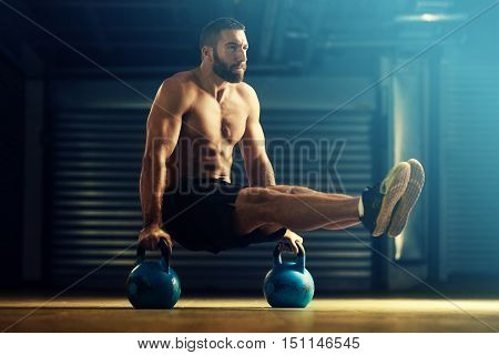 Young strong man is training by kettlebell.