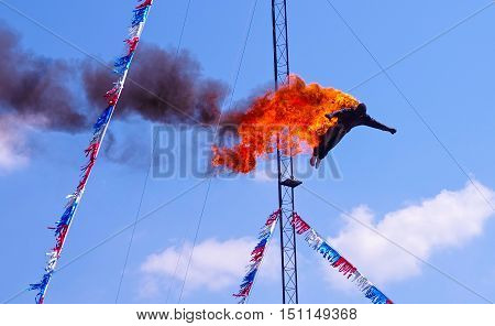 Fire Diver Daredevil Performing off the high dive platform head first into a pool of water at a show. Stuntman is dressed in a black fire protecting outfit. A very dangerous and extreme yet exciting athletic sport stunt.
