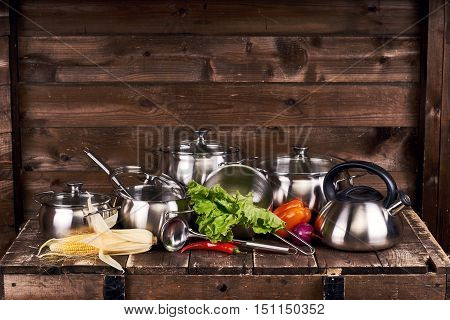 Different stainless steel pots, pans and laddles and fresh vegetables on old grunge wooden table against wood wall background poster