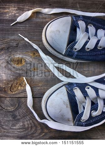 Old worn blue sneakers with white laces untied on an old wooden surface