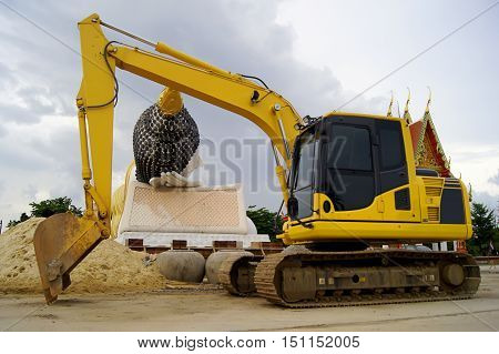 Reclining Buddha in front of a car construction backhoe