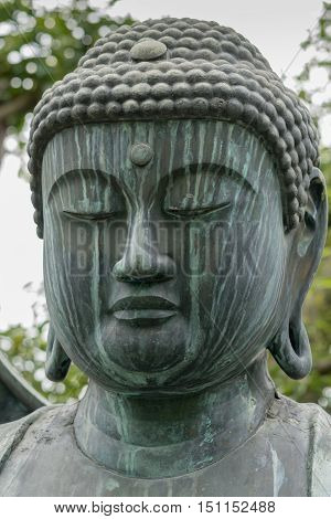 Kyoto Japan - September 15 2016: At the Shinnyo-do Buddhist Temple the stone statue of the meditating or Amithabha Buddha stands in the garden. Close-up of is head. Weather took toll.