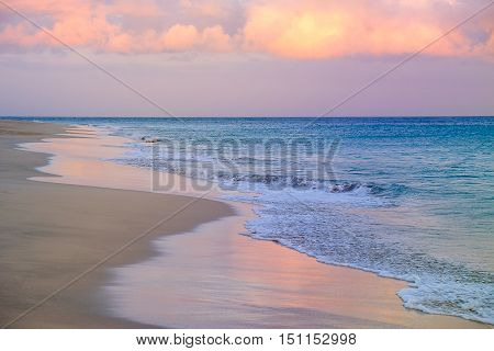 View on the sea with waves moving on the sand beach sky colored by sunset light.