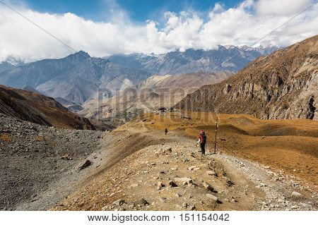 Trekker descending mountain on dirt path surrounded by wasteland. Muktinath region along Annapurna circuit trek in Nepal.