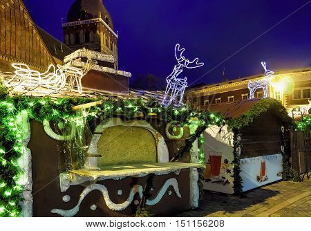 Christmas Stalls Decorated With Luminous Deer Statues In Old Riga