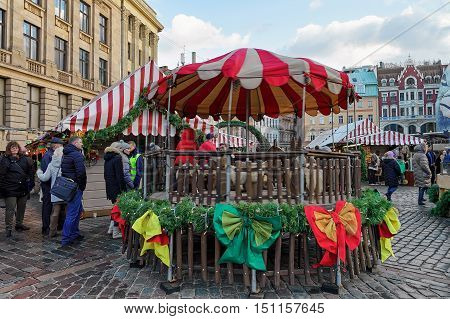 People At Carousel At Riga Christmas Market On Dome Square