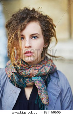Portrait Of Charming Girl With Dreadlocks In Her Cloak And Scarf On The Neck On A City Street.