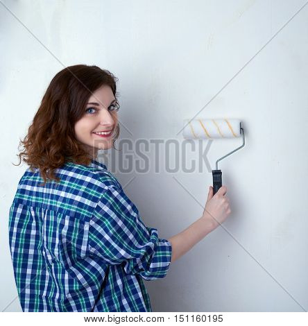 Smiling young woman in casual clothes in front of white unpainted wall working with paint roller, happy people and construction concept