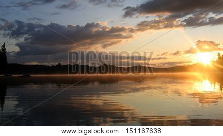 Sky and sunrise reflecting on a calm lake.