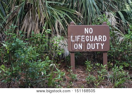 A sign near the beach warning that there is no lifeguard on duty