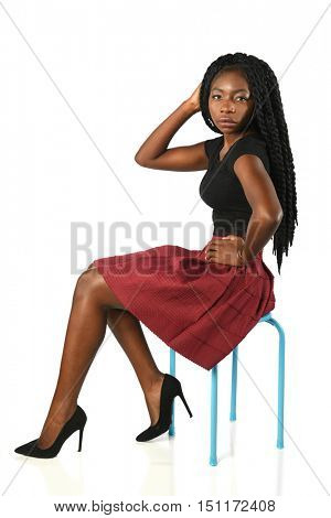 African American woman seated on stool isolated over white background