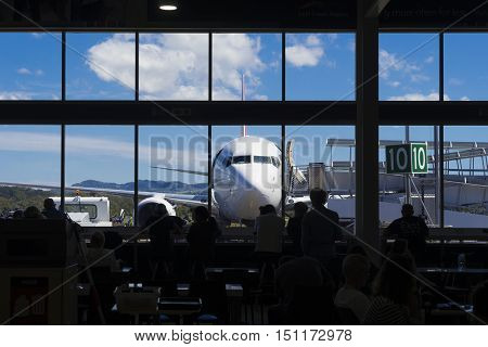 View of aircraft and people in the airport cafe in silhouette