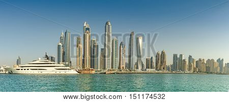 DUBAI, UAE - 09 OCTOBER 2016.  Panoramic Skyline of Dubai Marina with a luxury yacht in the foreground with azure gulf waters