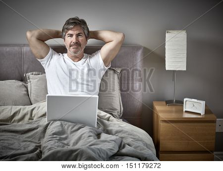 Man with laptop relaxing in bed.