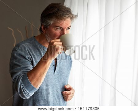 Handsome man with cup of tea near window.