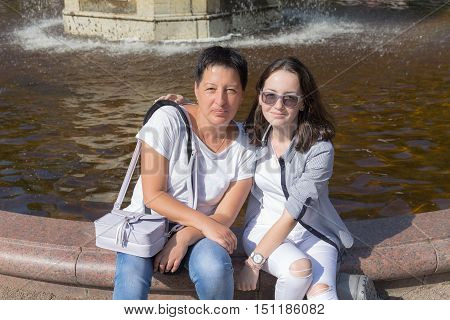 teenager girl with her mother at the fountain