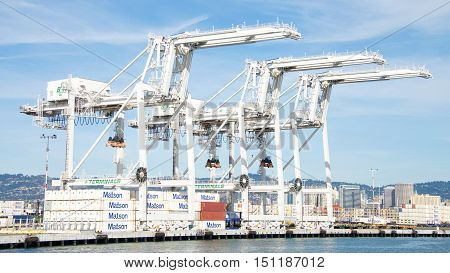Oakland CA - October 07 2016: Super Post Panamax cranes at the Port of Oakland. The giant cranes at the apex are roughly the height of a 24 story building and can weigh 1600 to 2000 tons each.